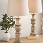 2 distressed cream skinny lamps with green plant sitting on table