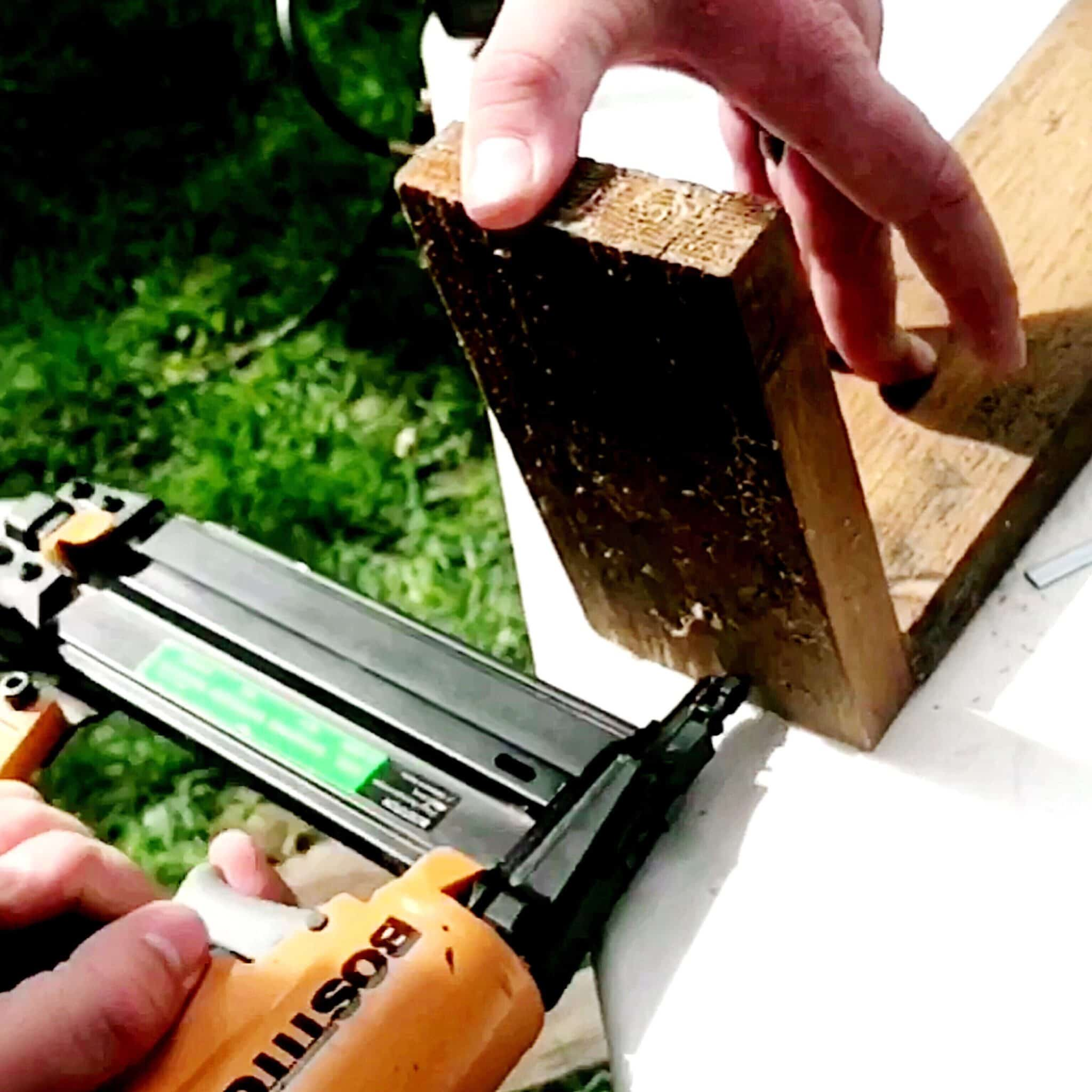Man using nail gun to attach 2 wood piece making a diy wood planter