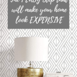 White and gray patterned wallpaper with white console table and lamp sitting on top on it with text overlay - The 1 easy step that will make your home look expensive.